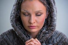 Kobiety modlenie z mrozem na jej twarzy Obrazy Stock