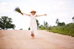 Kobiety na wiejskiej drodze z kwiatami Zdjęcia Royalty Free