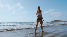 Kobiety nagiej stopy odprowadzenie na lato plaży zamyka w górę nogi młodej kobiety odprowadzenie wzdłuż fala woda morska i piasek zbiory wideo