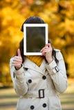 Kobiety nakrycia twarz z cyfrowej pastylki pustym ekranem Zdjęcia Royalty Free