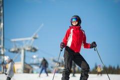 Kobiety narciarka z nartą przy winer kurortem w słonecznym dniu Obrazy Stock
