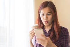 Kobiety niespodzianka na jej twarzy patrzeje telefon komórkowego obraz royalty free