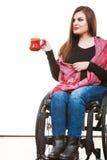 Kobiety nieważna dziewczyna na wózku inwalidzkim trzyma herbacianego kubek Fotografia Royalty Free