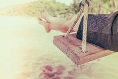 Kobiety noga na huśtawce przy tropikalną morze plażą - Filtrujący wizerunku proc obraz stock
