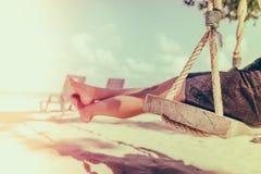 Kobiety noga na huśtawce przy tropikalną morze plażą - Filtrujący wizerunku proc zdjęcie royalty free