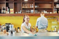 Kobiety obcieranie odpierający przy barem sklep z kawą obraz royalty free