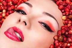 Kobiety oblizania wargi kłama w dzikich truskawkach Fotografia Stock