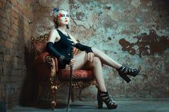 Kobiety obsiadania krzesło, mienie kordzik w jego ręce Fotografia Stock