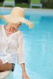 Kobiety obsiadanie basen stroną i ono uśmiecha się nad jej s Fotografia Royalty Free