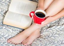 Kobiety obsiadanie na łóżku, tylko iść na piechotę i otwiera książkowego lying on the beach obok cieków widocznej, mienia czerwon Zdjęcia Stock