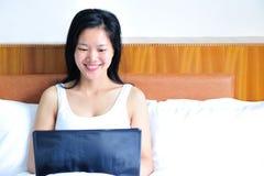 Kobiety obsiadanie na łóżku używać jej komputer obraz stock