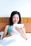 Kobiety obsiadanie na łóżku używać jej pastylkę Obrazy Stock