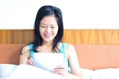 Kobiety obsiadanie na łóżku używać jej pastylkę Zdjęcia Royalty Free