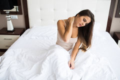 Kobiety obsiadanie na łóżku z bólem na szyi obrazy stock