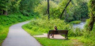 Kobiety obsiadanie na ławce blisko rzeki zdjęcia stock