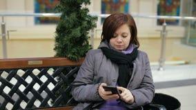 Kobiety obsiadanie na ławce i używać jej smartphone zbiory