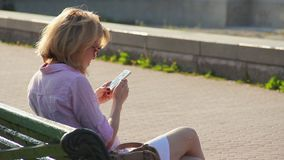 Kobiety obsiadanie na ławce w miasto parku, czytelnicza wiadomość z złą wiadomością na smartphone zdjęcie wideo