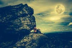 Kobiety obsiadanie na głazach, niebie z chmurnym i księżyc w pełni, Depresja ke zdjęcie stock
