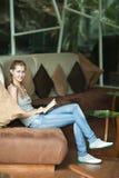 Kobiety obsiadanie na kanapie i czytania książce Fotografia Royalty Free