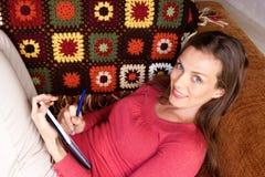 Kobiety obsiadanie na kanapie i writing w książce Fotografia Royalty Free