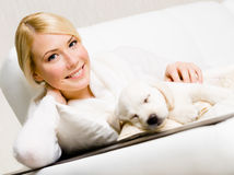 Kobiety obsiadanie na kanapie z sypialnym szczeniakiem zdjęcia stock
