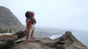 Kobiety obsiadanie na krawędzi falezy w pozie pies z widokami ocean, oddycha w dennym powietrzu podczas a zdjęcie wideo