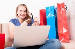 Kobiety obsiadanie na leżanki mienia laptopie wskazuje kartę Fotografia Royalty Free