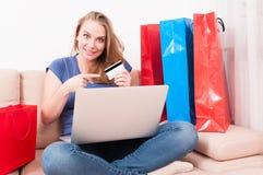 Kobiety obsiadanie na leżanki mienia laptopie wskazuje kartę Obrazy Stock