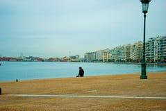 Kobiety obsiadanie na molu przy Leof Nikis ulicznym tłem przy Saloniki Grecja w Marzec 2018 Grecki styl życia blisko Biały Castle zdjęcia stock