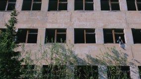Kobiety obsiadanie na okno zniszczony kondygnacja budynek z wiele łamanymi okno zbiory wideo