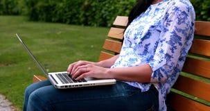 Kobiety obsiadanie na parkowej ławce używać laptop zbiory wideo