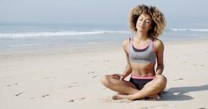 Kobiety obsiadanie na plaży w lotos pozie zbiory wideo