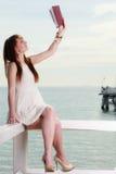 Kobiety obsiadanie na przeszkodzie blisko morza, czytelnicza książka zdjęcie royalty free