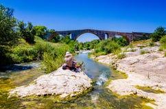 Kobiety obsiadanie na skale i obraz rzymski brid?owy Pont Julien w Provence zdjęcie royalty free