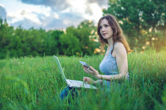 Kobiety obsiadanie na zielonej łące na tle zmierzch Pracować na laptopu radiu i patrzeć telefon fotografia royalty free