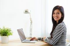 Kobiety obsiadanie przy jej biurkiem pracuje z laptopem zdjęcie stock