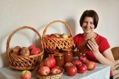 kobiety obsiadanie przy stołem z świeżymi jabłkami i jabłczanym dżemem zdjęcia stock