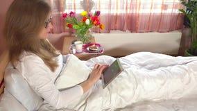 Kobiety obsiadanie w łóżkowym używa pastylka komputerze Śniadanie i kwiaty na spiżarni zbiory