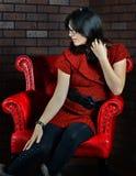 Kobiety obsiadanie w czerwonym krześle zdjęcia royalty free