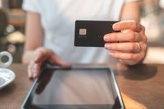 Kobiety obsiadanie w kawiarni i mienia karcie kredytowej w ręce zdjęcie royalty free