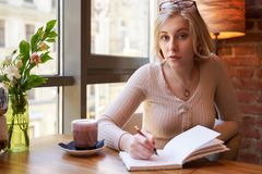Kobiety obsiadanie w kawiarni przy wielkim panoramicznym okno Młoda dziewczyna pisze ważnych rzeczach w notatniku obraz royalty free