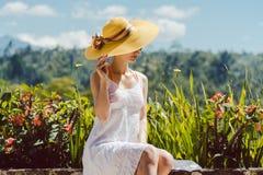 Kobiety obsiadanie w tropikalnym ogr?dzie cieszy si? s?o?ce obrazy stock