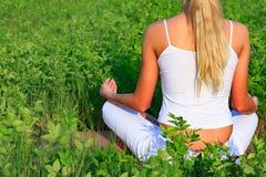 Kobiety obsiadanie w zielonej trawie fotografia stock