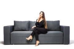 Kobiety obsiadanie z rękami na podbródku na kanapie na białym tle zdjęcia royalty free