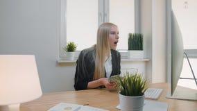 Kobiety odświętności sukces w biurze Elegancki blond żeński obsiadanie przy miejsca pracy mieniem w ręka pliku gotówkowy patrzeć zbiory wideo