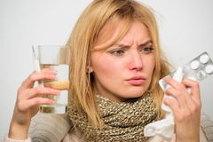 Kobiety odzieży ciepły szalik ponieważ choroba lub grypa Dziewczyna chwyta szkła wody pastylki i termometr nosowe krople Dostawać fotografia stock