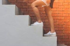 Kobiety odzieży czerni bielu i koszulki skróty, ona chodzą w górę betonowych schodków na zewnątrz budynków z czerwonym ściana z c Obraz Royalty Free