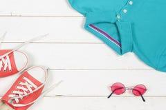 Kobiety odziewa set i akcesoria na nieociosanym drewnianym tle Sporty koszulka i sneakers w jaskrawych kolorach Odgórny widok Obraz Royalty Free
