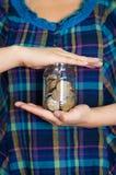 Kobiety okładzinowa kamera, mienie szklany słój z monetami inside Fotografia Royalty Free