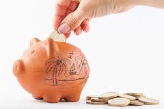 Kobiety oszczędzania pieniądze w tradycyjnego glinianego prosiątko b Zdjęcia Stock